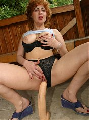 Older babe plays with her big boobs and pulls her panties aside to sit on a huge dildo
